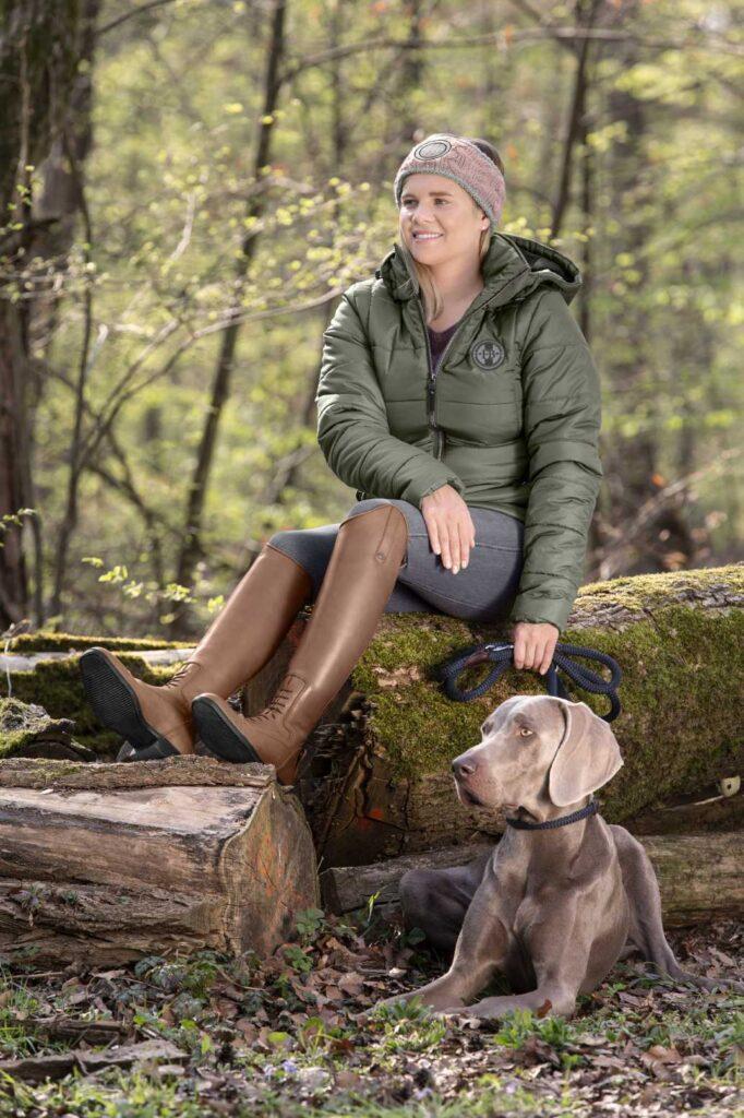 Reiterin mit braunen Lederreitstiefeln beim Waldspaziergang mit ihrem Hund.