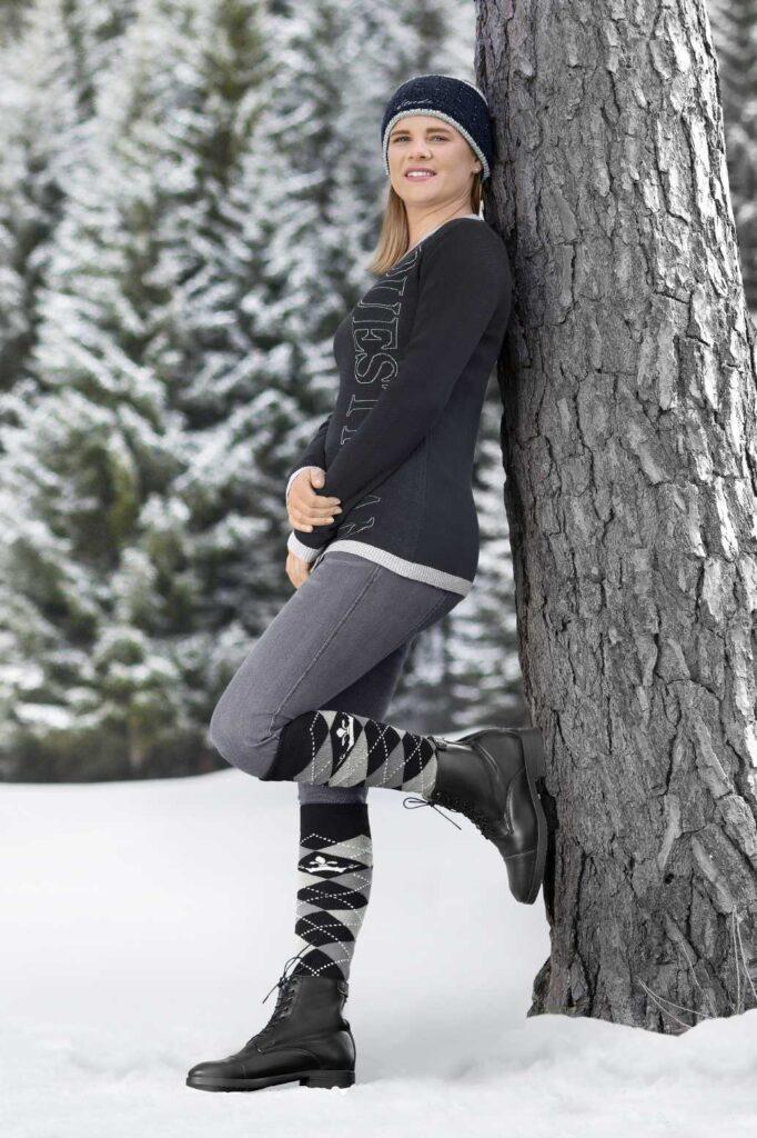 Reiterin im Schnee an Baum gelehnt mit Stiefeletten aus Kunstleder.