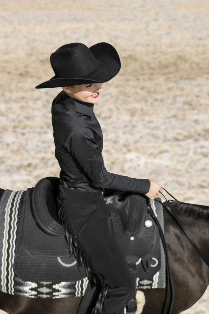 Westernreiterin mit Westernhut in schwarzem Showhemd mit schwarzen Westernchaps.